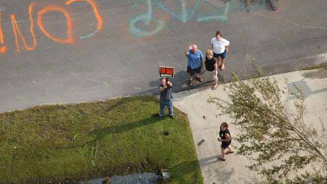 Bay St. Louis, Miss., residents stand outside their damaged homes on Wednesday, Aug. 31, 2005.