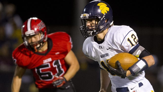 Wausau West quarterback Chandler Fochs heads downfield with East's Jay Lee in pursuit.