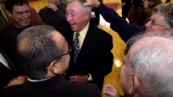 Bobby Wanzer, the first basketball coach at St John Fisher, is celebrated by basketball alumni at the dedication of the court in his name at Fisher. James Leary, far right, class of '68, gives him a pat on the head on Feb. 21, 2006.