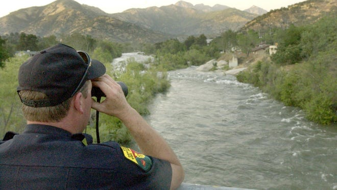 Don Abbott, fire apparatus engineer with CDF, searches for a missing person swept away in the current of the Kaweah River just north of North Fork Bridge in Three Rivers,