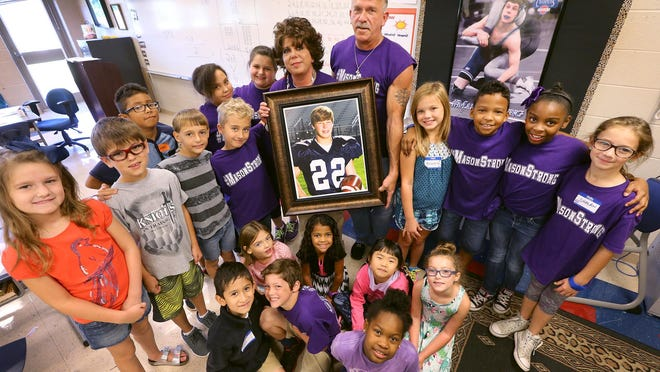 Melanie Heston and her husband, John Heston, hold a photograph of her son, Mason, who died last year. They are surrounded by her third-grade class at Scales Elementary.