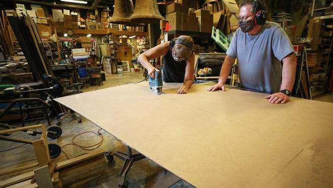 With help from volunteer Dale Gilbert, assistant technical director Kathy Kohl cuts a piece of flooring to size for the stage at Weathervane Playhouse on Wednesday in Akron.