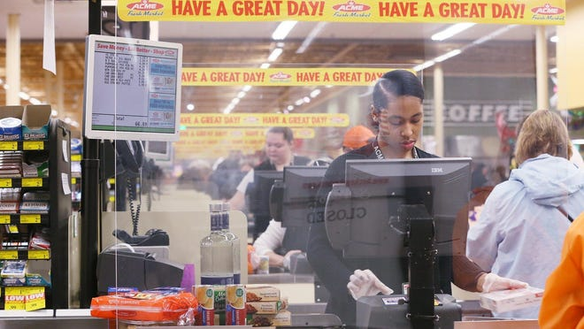 Acme cashier Kay'la Crawford, 17, rings up a customer behind newly installed plastic guards at Acme No. 2 in Akron's Ellet neighborhood. Grocery store executives say in-store safety modifications such as Plexiglass panels at checkouts and social distancing measures are likely to be around for a while.