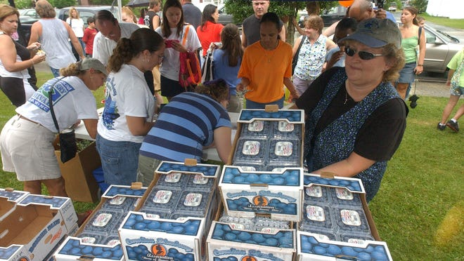 In this photo from 2005, Kim Hunter grabs some blueberries for a customer at the N.C. Blueberry Festival in Burgaw. The event has been canceled for 2021. [STARNEWS FILE PHOTO]