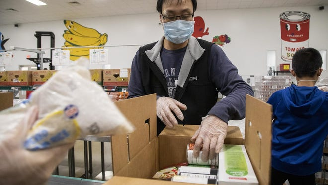 """Xiaohu Zhang and other volunteers pack items into """"emergency boxes"""" at the Central Texas Food Bank on March 16."""