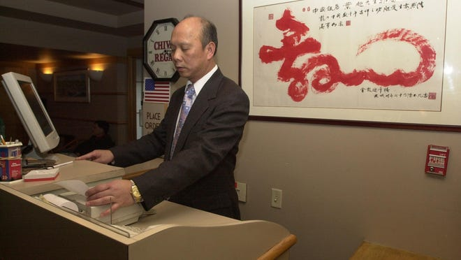 Louis Yip, owner of the China Inn in Pawtucket, rings up a bill on the cash register as he oversaw business at the restaurant on Christmas day in an otherwise undated photo.