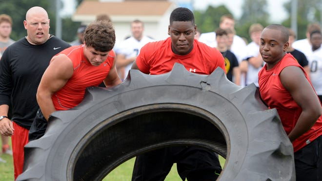 University School of Jackson coach Ryan Wernquist looks on as Elijah Moore, Trey Smith and Sean Reid particiapte in the tire flip during the Fellowship of Christian Athlete's football camp Wednesday.