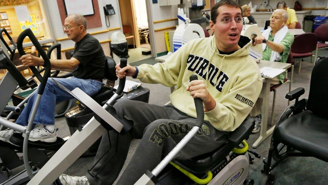 Cody Lehe does exercises that are part of the therapy Wednesday in the cardiopulmonary rehab facility at Franciscan St. Elizabeth Central. Cody, who is now 25, was injured eight years ago when he was a football player at Frontier High School. He sustained a hard hit late in a first round sectional game against Caston. Tests showed nothing out of the ordinary, but four days later in practice he sustained a severe traumatic brain injury.
