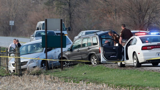 Law enforcement officers from several counties gather at the scene of a police action shooting Thursday, April 9, 2015, on U.S. 421 about a half mile north of Monon. What began as a robbery in Watseka, Illinois, turned into a multi-county chase in Indiana, ending with the armed robbery suspect being shot after he fired at police. A hostage taken by the robbery suspect was transported to IU Health White Memorial Hospital with unknown injuries.