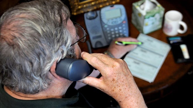 This photo illustration on telephone scams shows a senior citizen preparing to write a check after receiving a bogus call from someone requesting money.