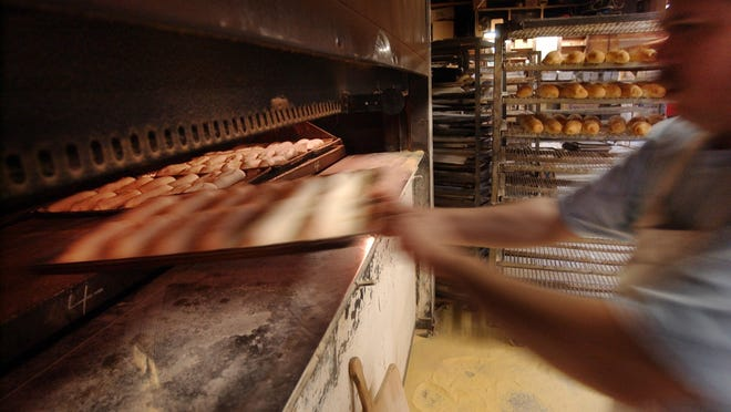 An employee slides trays of dough for hoagie rolls into the oven at Serpe & Sons in 2004.