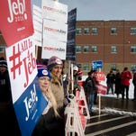 Supporters hold signs in favor of Republican presidential candidate, former Florida Gov. Jeb Bush as voters arrive at a polling site inside Bedford High School, on Feb. 9, 2016, in Bedford, N.H.