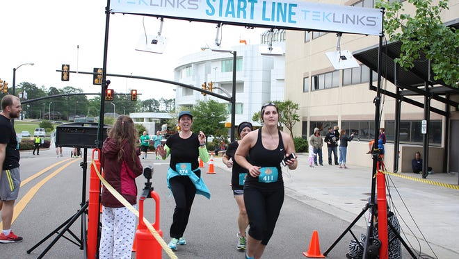 Melissa Hanberry of Hattiesburg (# 374) crosses the finish line at Hattiesburg Clinic's 2015 Rise & Shine Half-Marathon & 5K in Hattiesburg. Hanberry ran in honor of her teenage daughter, who is a cancer survivor.
