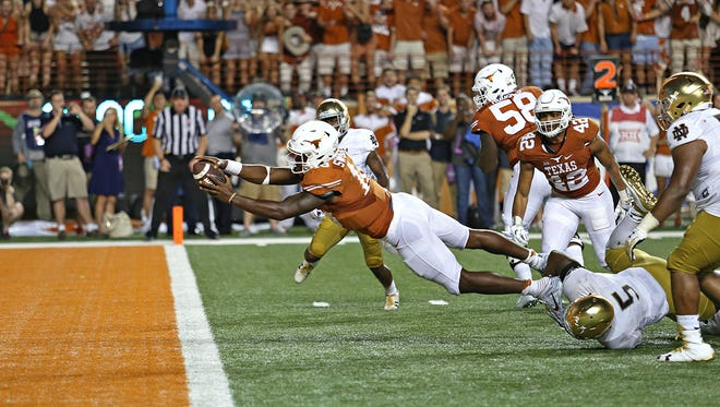 Texas quarterback Tyrone Swoopes (18) dives for a touchdown during the second overtime of an NCAA college football game against Notre Dame on Sunday in Austin. Texas won 50-47.