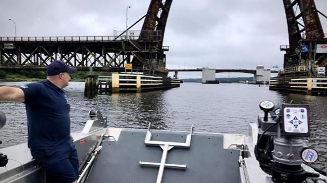 Fall River Fire Capt. Frank O'Reagan stands near the bow ramp of a new rescue boat as it approaches the former Brightman Street Bridge. The city's Fire Department has seen a rise in boating-incident calls this summer, according to Capt. Jim Furtado, the department's spokesman.