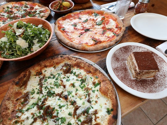 The white pizza and margherita pizza along with an arugula salad and tiramisu are pictured at Pizzeria La Rosa in New Rochelle, Nov. 2, 2017.