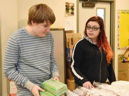 John, a resident, helps organize supplies as Ashley Friedel, a teacher aide, supervises at the Anderson Center for Autism in Staatsburg.