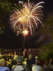 Spectators view the fireworks display over Burlington Harbor from a grassy hillside in Battery Park on Saturday, July 3, 2004.