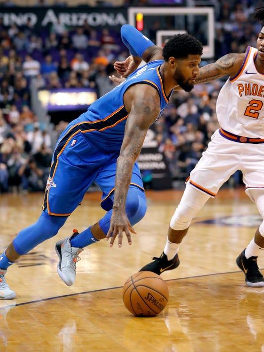 Oklahoma City Thunder forward Paul George drives against Phoenix Suns guard Elfrid Payton (2) during the first half of an NBA basketball game Friday, March 2, 2018, in Phoenix. (AP Photo/Matt York)
