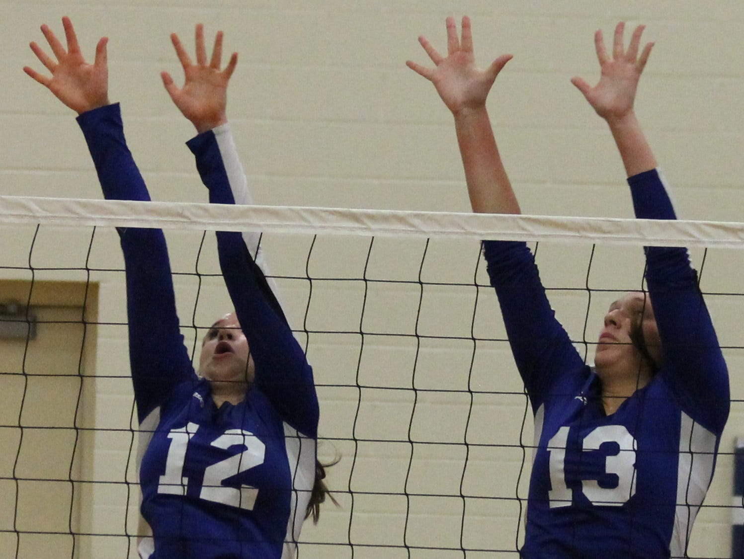 Williamsburg's Emily McKibben (12) and Carly Wagers (13) go up for a block against CNE Tuesday.