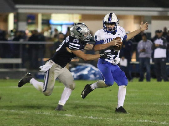 Zanesville's Ben Everson is chased by a Granville defender during the visiting Blue Devils' 30-7 loss on Friday night.