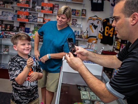 Grand Slam owner Nathan Burns takes a picture of Jameson Patrick, a MTCS first-grader, who discovered a special card in a package he had just opened as mother Jana Patrick looks on.