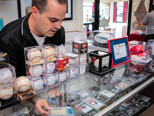 Nathan Burns places an item autographed by Major League Baseball Hall of Famer Ty Cobb back into a display case at Grand Slam Collectibles in Murfreesboro.