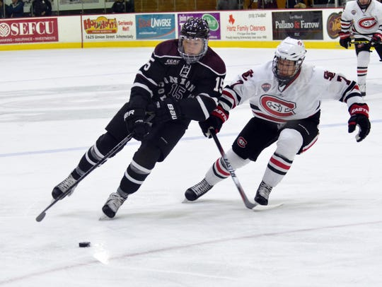 Union's Spencer Foo (left) carries the puck with St.