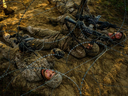 A team of four recruits work over, under and around obstacles covered in barbed wire toward an objective during The Crucible on Thursday October 20, 2016 at the Marine Corps Recruit Depot in Parris Island, SC.