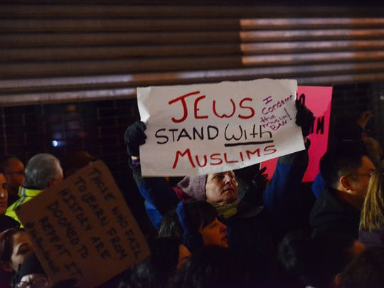 Protesters holding up signs during a ally against refugee, Muslim ban in Jersey City on Monday night.