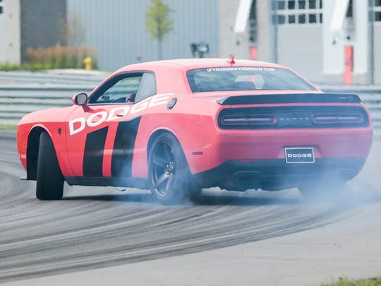 Professional driver Andy Thurman takes a media member in a 2017 Dodge Challenger SRT Hellcat for a thrill ride during the Roadkill Nights preview event at M1 Concourse Race Track in Pontiac, Friday, August 11, 2017.