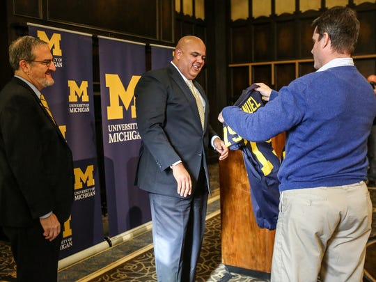 Warde Manuel, the new U-M athletic director, accepts a jersey from U-M Football Head Coach Jim Harbaugh, while U-M president Mark Schlissel, left, looks on, during a press conference at the Michigan Union on campus in Ann Arbor, Mich. on Friday, Jan. 29, 2016.