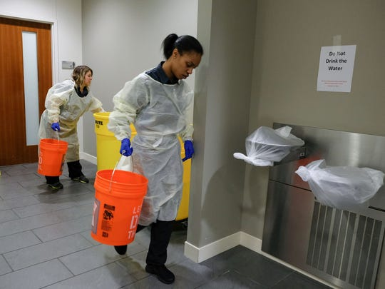 Providence Park Hospital housekeeping members Marquitta Odell and Lisa Emery gather buckets of water to flush toilets at Providence Park Hospital in Novi on Tuesday October 24, 2017 after a boil advisory was issued following a water main break occurred in Farmington. Water fountains are covered in the hospital after the break caused the advisory for 11 Oakland County communities.