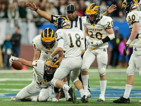 Clarkston players celebrate after recovering a fumble by West Bloomfield during the first half of the MHSAA Division 1 championship game at Ford Field in Detroit, Saturday, Nov. 25, 2017.