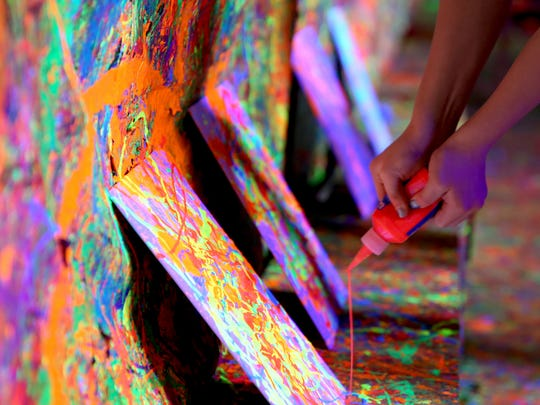 Riley Bond, 13, of Albany pours paint on a canvas inside the Splatter Box at the Albany Art Studio.