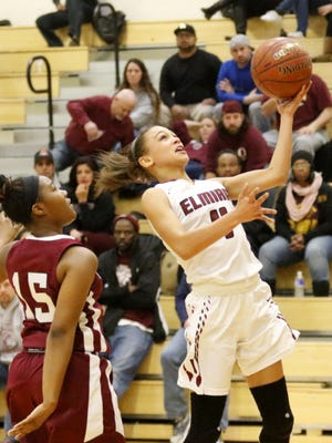 Elmira's Kiara Fisher goes in for a layup as Ossining's Adriana McFadden defends Saturday during a Class AA girls basketball regional final at Johnson City High School.