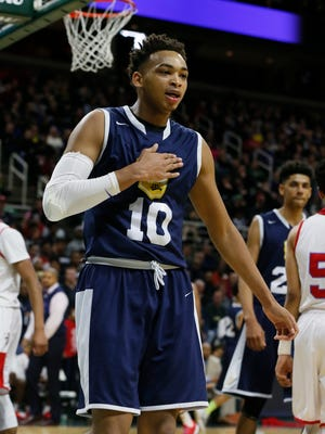 Saginaw Arthur Hill's Eric Davis pounds his chest after being fouled in the first half of a 73-61 win over Lansing Everett in a Class A semifinal basketball game on Friday, March 27, 2015, in East Lansing.