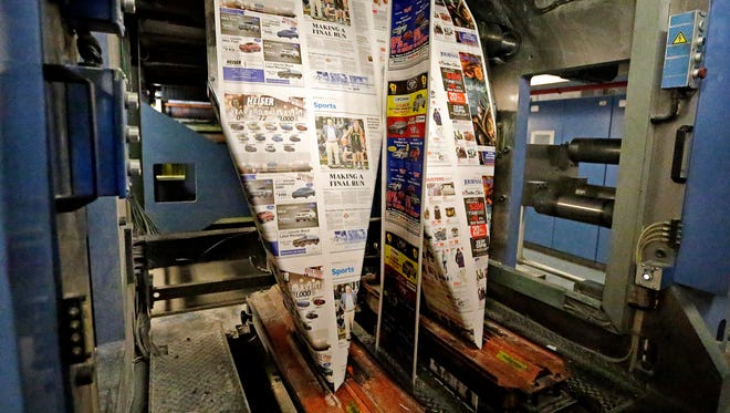 Newsprint heads into the folding machine to produce the Thanksgiving Day Milwaukee Journal Sentinel, the largest paper of the  year, in this 2017 photo.
