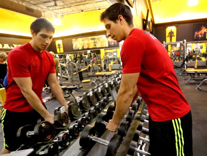 Ethan Vanatta a personal trainer at Gold's Gym in puts weights back as his client takes a quick break between exercises, on Friday, August 8, 2014.