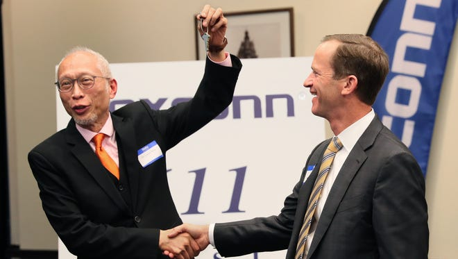 Foxconn's Louis Woo (left) has fun with accepting the keys to the the building at 611 E. Wisconsin from Northwestern Mutual's Vice President of Real Estate Tom Zale.