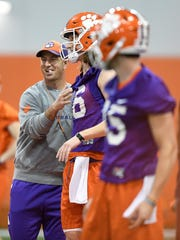 Clemson head coach Dabo Swinney laughs with quarterback Trevor Lawrence (16) during the Tigers opening day of spring practice on Wednesday, February 28, 2018.