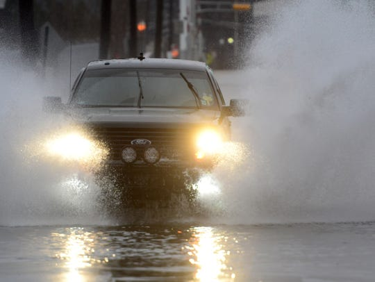A car drives through the flood waters on W Fort Lee