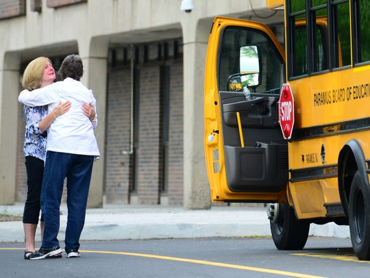 A bus driver, left, is hugged by a woman the morning