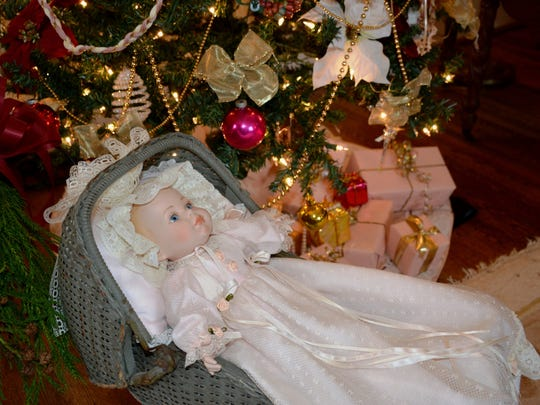 Pink packages, a well-dressed tree, and an antique doll and wicker carriage set the scene in the parlor of the historic Kilgore-Lewis House.
