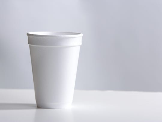 A styrofoam cup sitting on a desk.