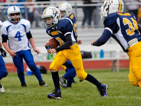 Algonac Muskrats' Nathan Stringer, 11, runs the ball during a Thumb Area Football League game September 13, 2014 at Algonac High School.
