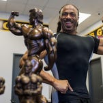 Bodybuilder Timothy Garrett poses for photographs with his trophies from National Phyisique Committee Louisiana Championships trophies at Gold's Gym in Breaux Bridge, La., Tuesday, July 21, 2015.