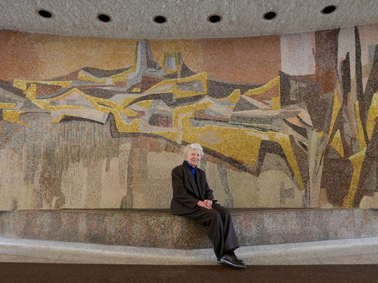 """Artist Marjorie Kreilick, 93, sits in front of """"Forward,"""" the largest of the mosaics she created throughout the Milwaukee State Office Building at 819 N 6th St."""