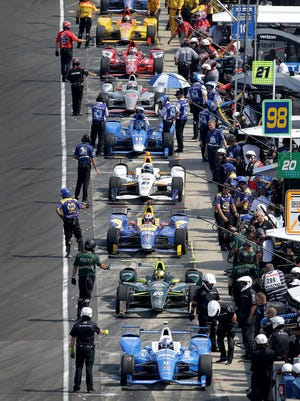 IndyCar drivers wait to get back onto the track following a yellow flag during Carb Day Friday, May 26, 2017, at the Indianapolis Motor Speedway