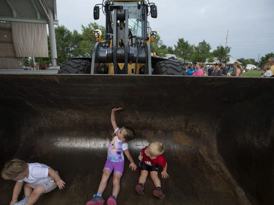 Gabbi Loos stretches herself inside the bucket of a bull dozer pictured with Brentley Tonie on the left and Mitchell Oestreich during the Touch A Truck & Family Night at the Leach on Saturday, Aug. 8, 2015.